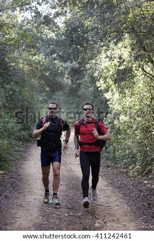 Men running along a forested trail