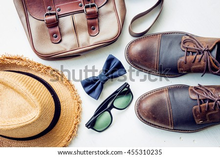 Men's accessories outfits with brown leather shoes, bag, hat, sunglasses, and bow tie, top view, flat lay on wooden board background
