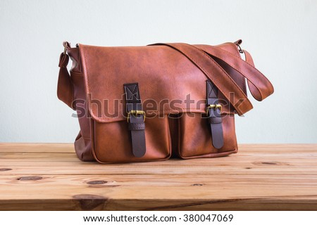 Men's accessories with brown leather bags on wooden table over wall background - stock photo