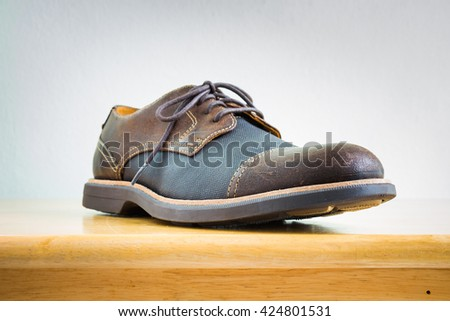 Men's accessories with brown leather shoes on wooden table, bar or counter over white wall background - stock photo