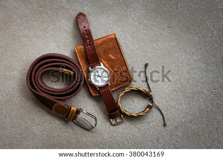 Men's accessories with brown leather wallet, belt and watch on gray background - stock photo
