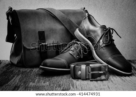 Men's accessories with classic shoes, leather bag and belt on wooden table over grunge background, still life style, black and white - stock photo