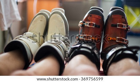 Men's and women's naked legs in ski boots - stock photo