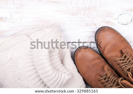 Men's autumn and winter casual clothes wool sweater and shoes on old white wooden background. Top view - stock photo