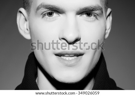 Men's beauty concept. Black and white close up portrait of young handsome man smiling over gray background. Studio shot - stock photo