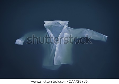 Men's business button up shirt floating or sinking in water - stock photo