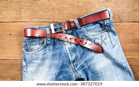 men's casual jeans and brown leather belt on wooden board - stock photo