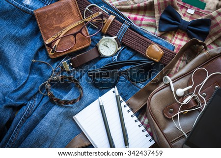 Men's casual outfits background, brown plaid shirt, bow tie, blue jean, brown bag and accessories - stock photo