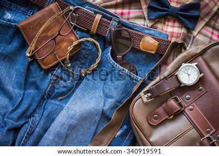 Men's casual outfits background, brown plaid shirt, bow tie, blue jeans, brown bag and stationary - stock photo