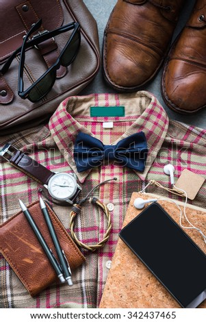 Men's casual outfits background, brown plaid shirt, bow tie, boots, brown bag and stationary - stock photo