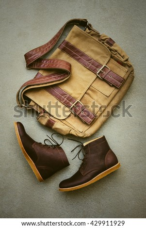 Men's casual outfits with brown boots and brown handbag on gray grunge background