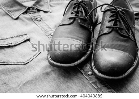 Men's casual outfits with jeans shirt and shoes background, black and white - stock photo