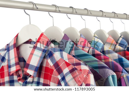 Men's colorful checked shirts on white hangers, close-up, shallow dof, white background - stock photo