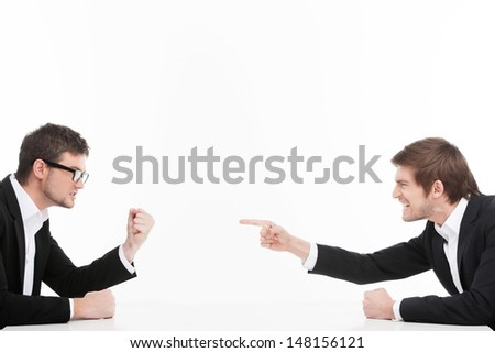 Men's confrontation. Two angry young business people shouting and blaming each other while isolated on white - stock photo