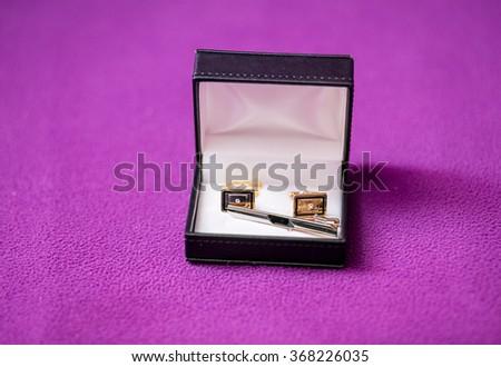 Men's cufflinks in the box on purple fabric. - stock photo