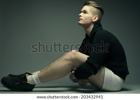 Men's fashion concept. Portrait of a young fashionable man in trendy casual clothes and underwear sitting over gray background. Hipster style haircut. Copy-space. Studio shot - stock photo