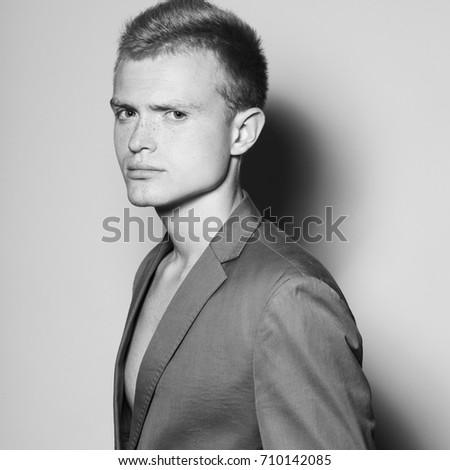 Men's fashion concept. Portrait of gorgeous blond fashion model in gray jacket posing over gray background. Close up. Monochrome studio shot