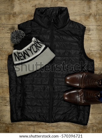 Men's fashion flat lay of a black gilet, wool beanie and leather shoes on a wood background