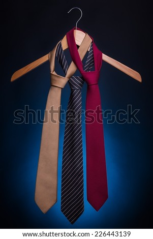 Men's fashionable ties on a hanger. On a blue background. - stock photo