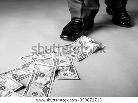 Men's feet and dollar banknotes on the floor - stock photo