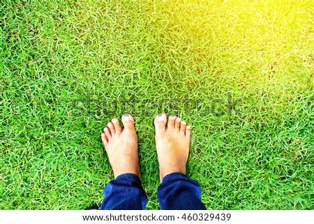 men's feet standing on green grass,