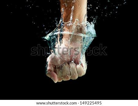 Men's fist punching water splash - stock photo