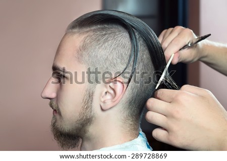 Men's hairstyling and haircutting in a barber shop or hair salon. - stock photo