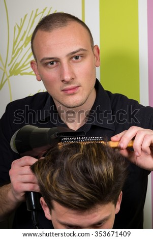 Men's hairstyling and haircutting with hair clipper and scissor in a barber shop or hair salon.