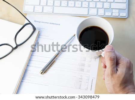 Men's hand holding coffee cup analyzing financial statement - stock photo