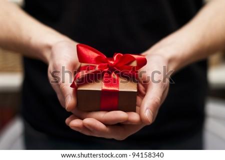 Men's hand holding gift box - stock photo