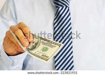 Men's hand holding money american hundred dollar bills. Hand of businessman offering money.  - stock photo