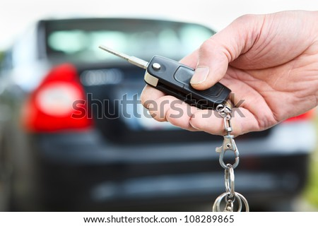 Men's hand presses on the remote control car alarm systems - stock photo