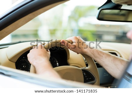 Men's hands hold a wheel of a car, the car in the showroom assessment - stock photo