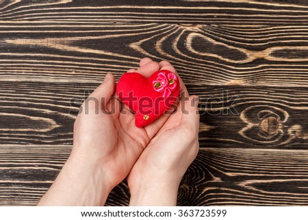 Men's hands holding red heart over wooden background - stock photo