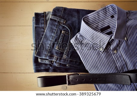 Men's jeans, shirt and belt decomposed on a wooden background - stock photo