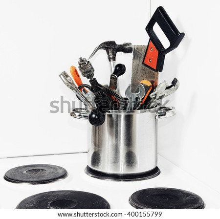 Men's kitchen. Hand tools in a saucepan on the stove - stock photo