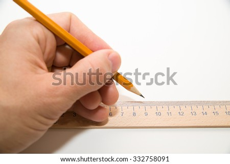 Men's left hand holding a pencil on a white