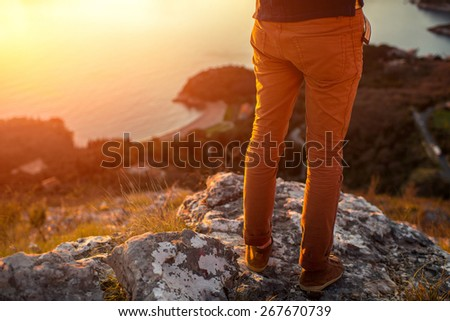 Men's legs in the brown shoes standing on the mountain on the sea scape background on the sunset - stock photo
