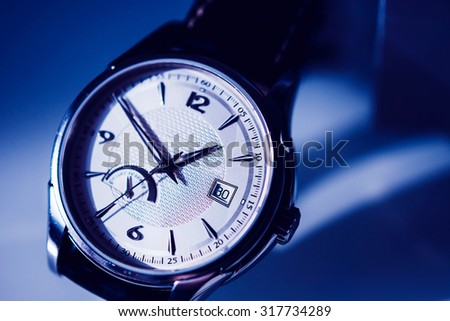 Men's luxury watch isolated on a pleasant blue background - stock photo