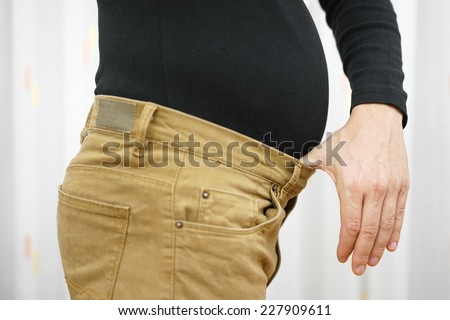 Men's pants are too tight due to the higher weight - stock photo