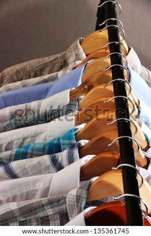 Men's shirts on hangers on gray background - stock photo