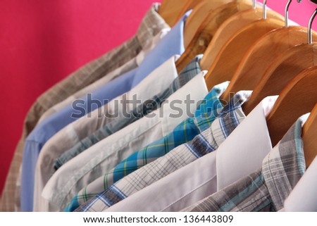Men's shirts on hangers on pink background - stock photo