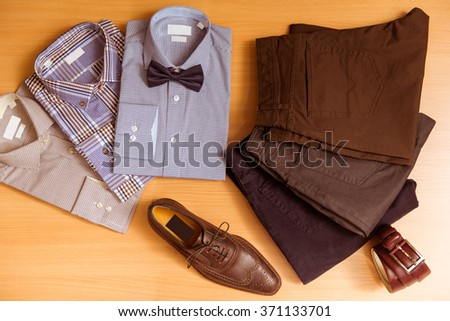 Men's shirts, trousers, bow tie, belt and shoes lying on wooden background - stock photo