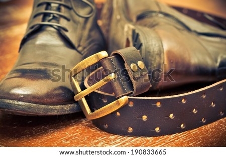 men's shoes and leather belt brown with gold buckle. cowboy style. Photo tinted yellow - stock photo