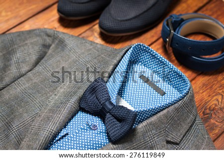 Men's suit, belt and footwear on a wooden background - stock photo