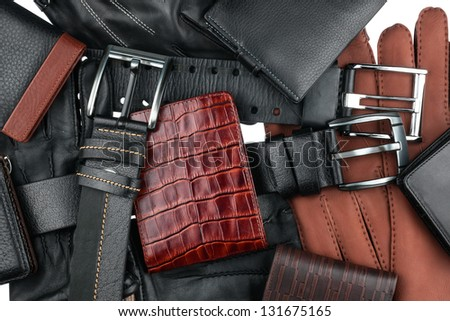 Men's wallet lying on the belts and gloves isolated on white - stock photo