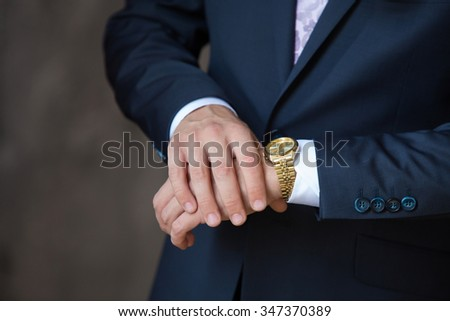 men's watch on the man's hands in a suit - stock photo