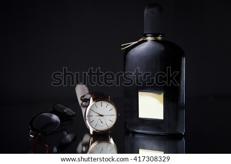 Men's watches, perfume and glasses on black background - stock photo
