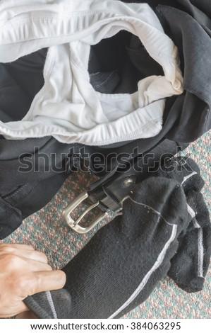 Men's wear sock ,casual outfits, black slack white underwear and black belt hanging floor background.Bad habit concept. - stock photo