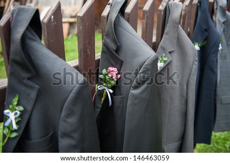 Men's wedding jackets hanging in a row on a wooden fence. Shallow DOF - stock photo
